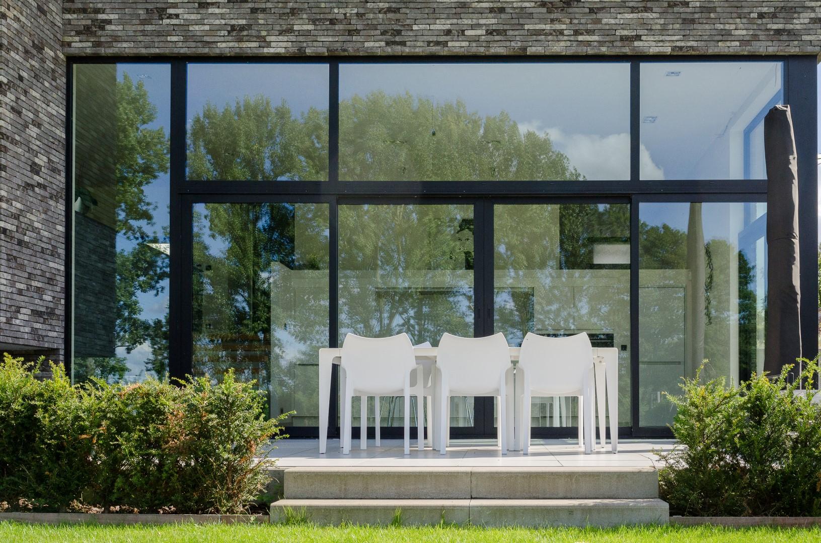 Detail panoramisch raam aan de achterzijde van de strakke woning in Herfelingen