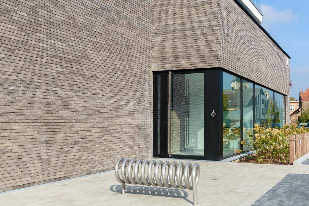 Detail inkom met fietsrek moderne nieuwbouw voor medisch centrum in Ternat