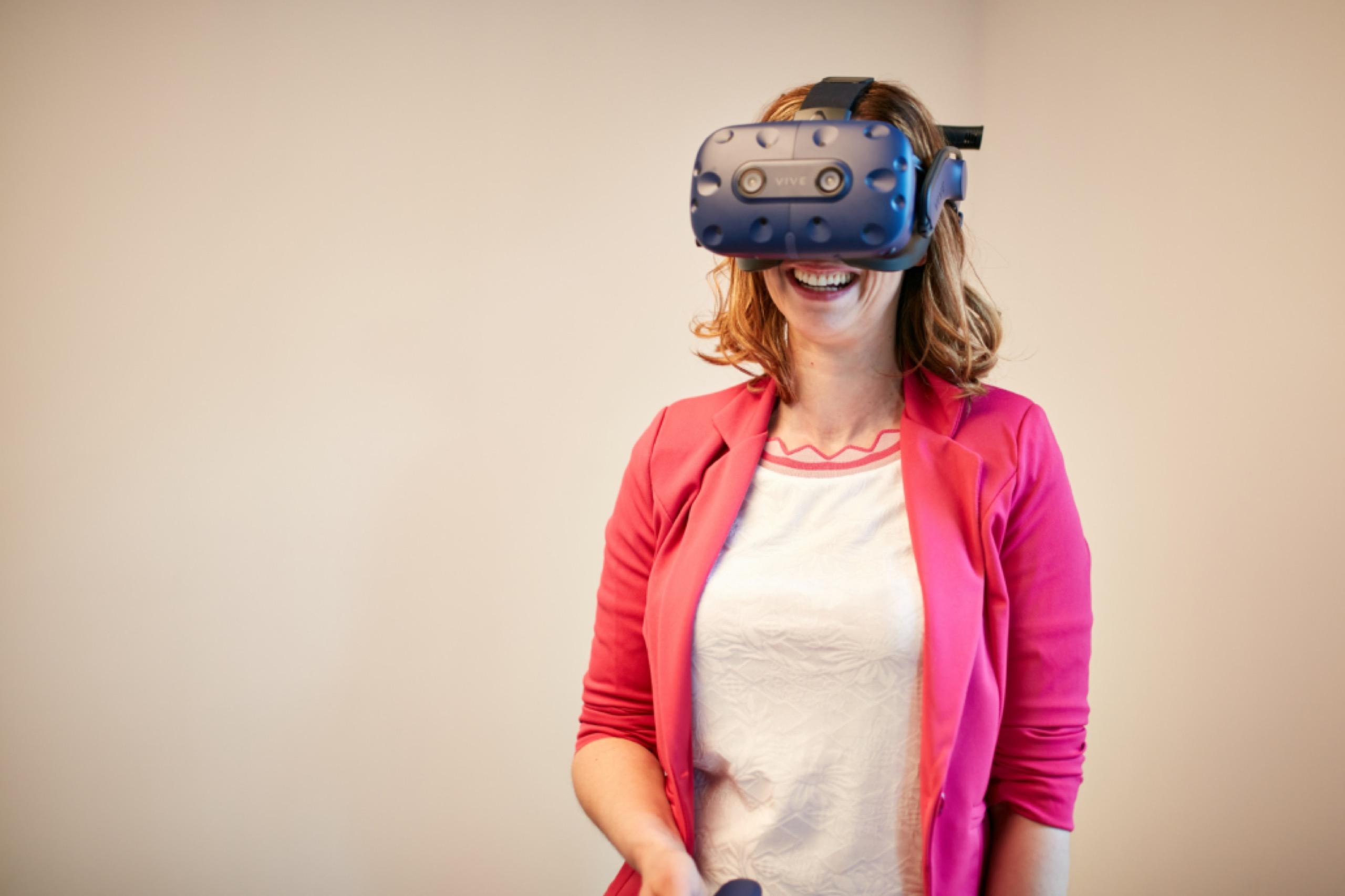 Vrouw draagt VR bril en geniet van een virtuele beleving van haar bouwproject